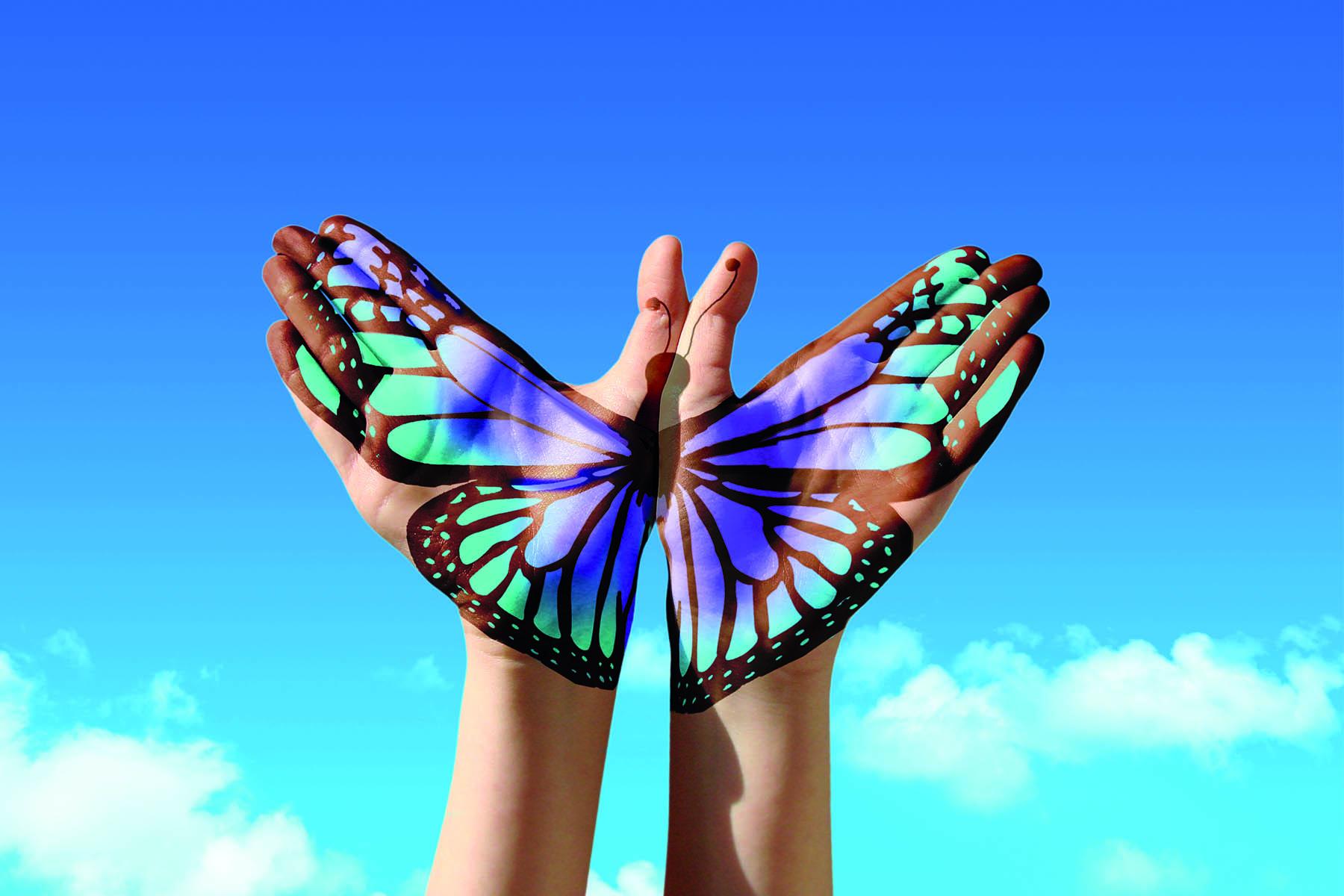 En målad fjäril på två öppna handflator som öppnar sig mot himlen