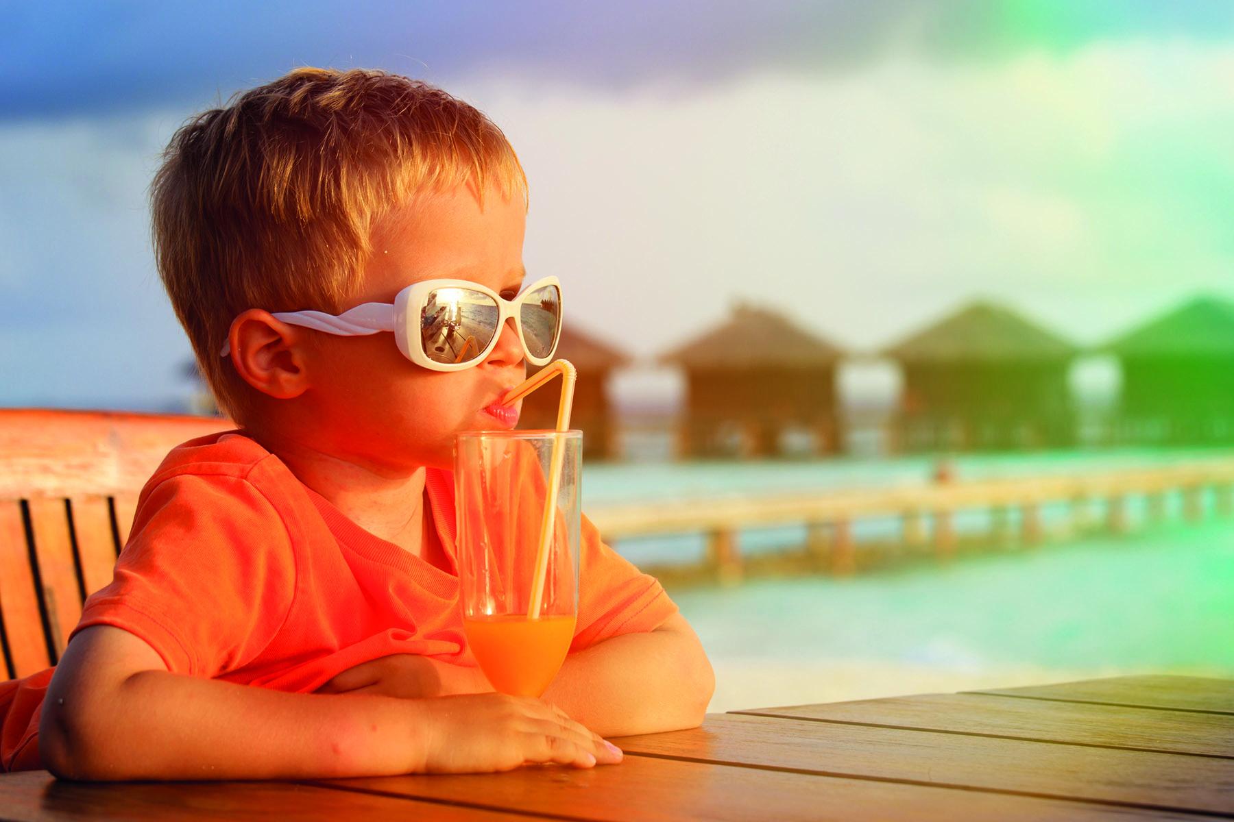 En pojke mes solglasögon dricker juice i morgonsolen