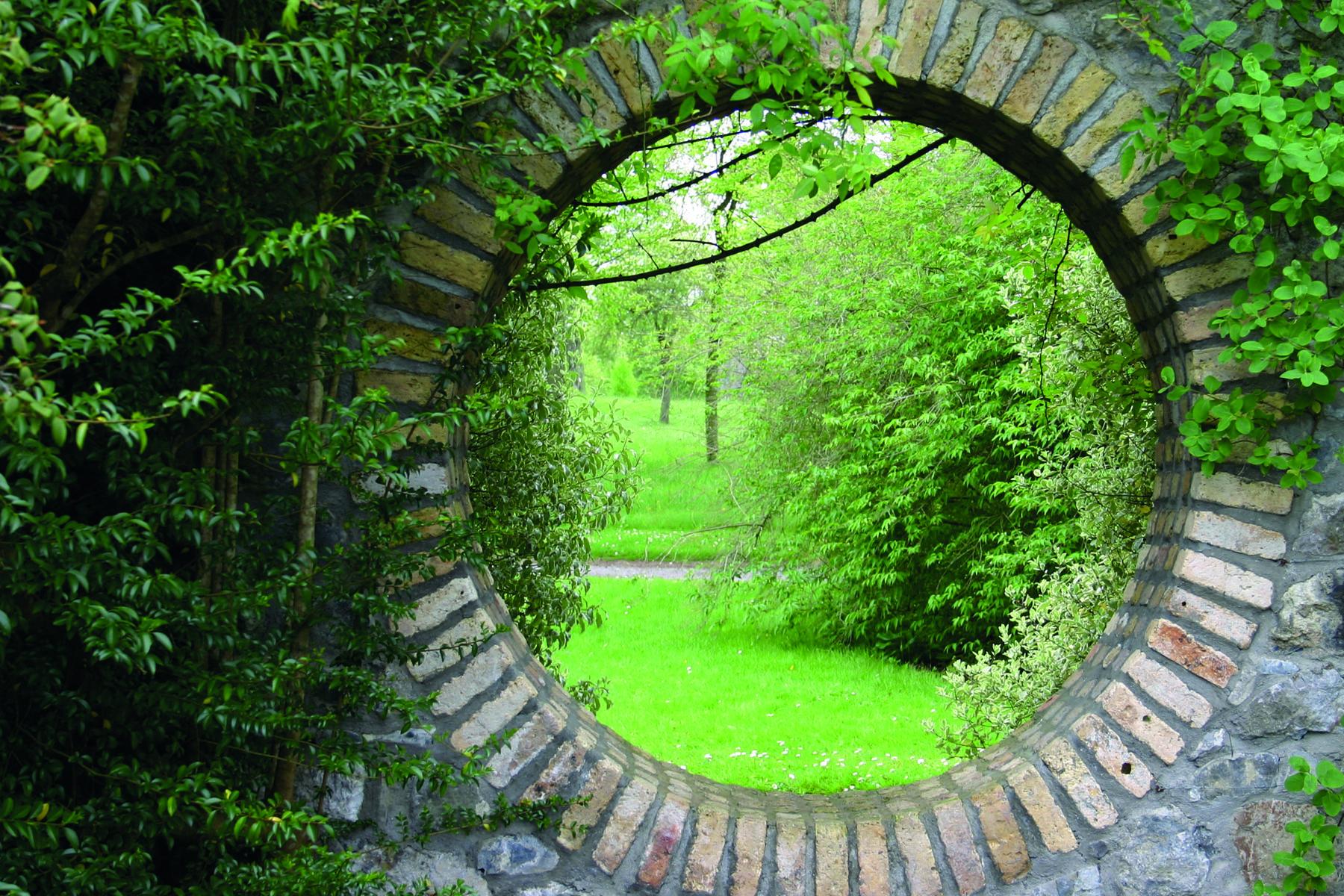 Ett runt fönster mot en vilsam trädgård