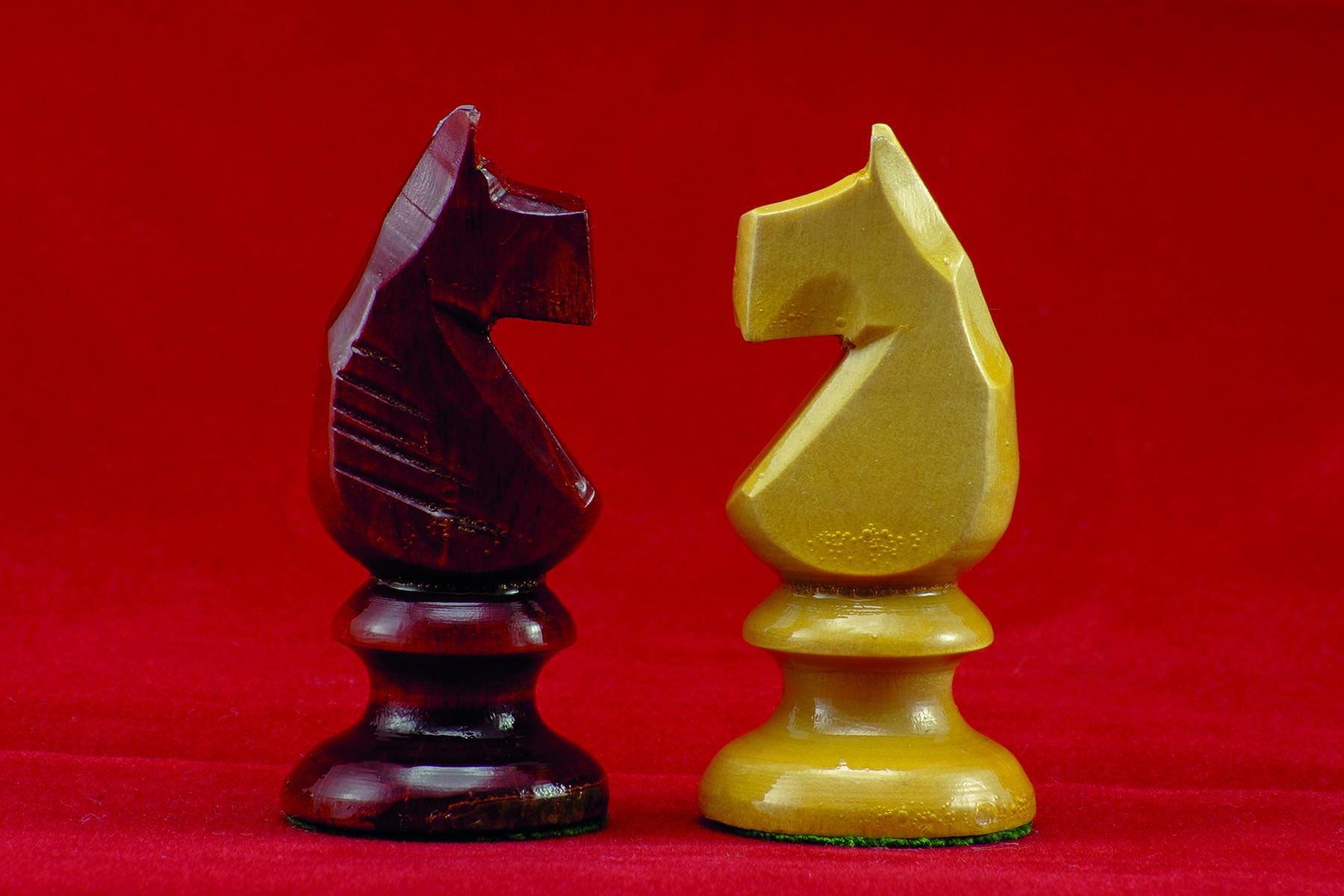En röd och en vit springare i schack står öga mot öga