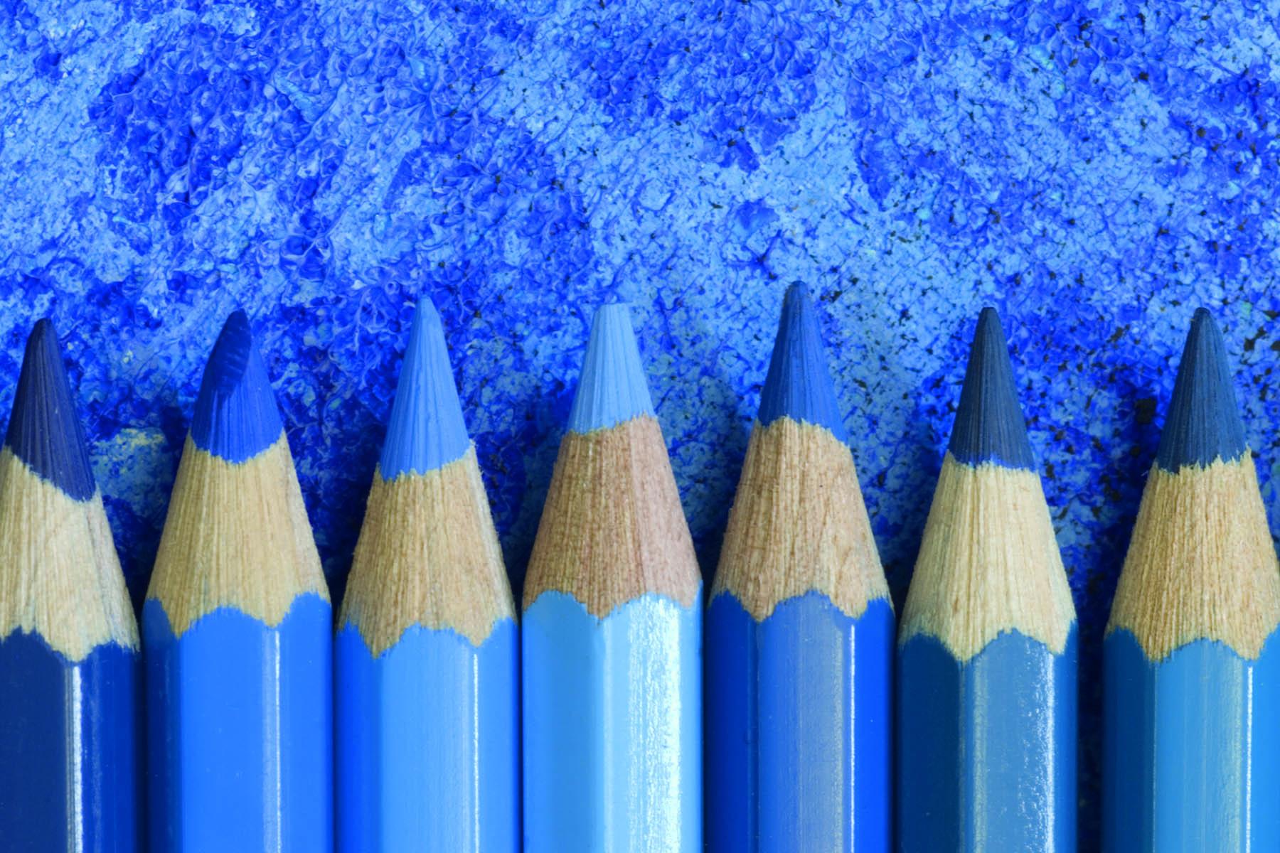 Blå blyertspennor ligger på rad med spetsarna uppåt