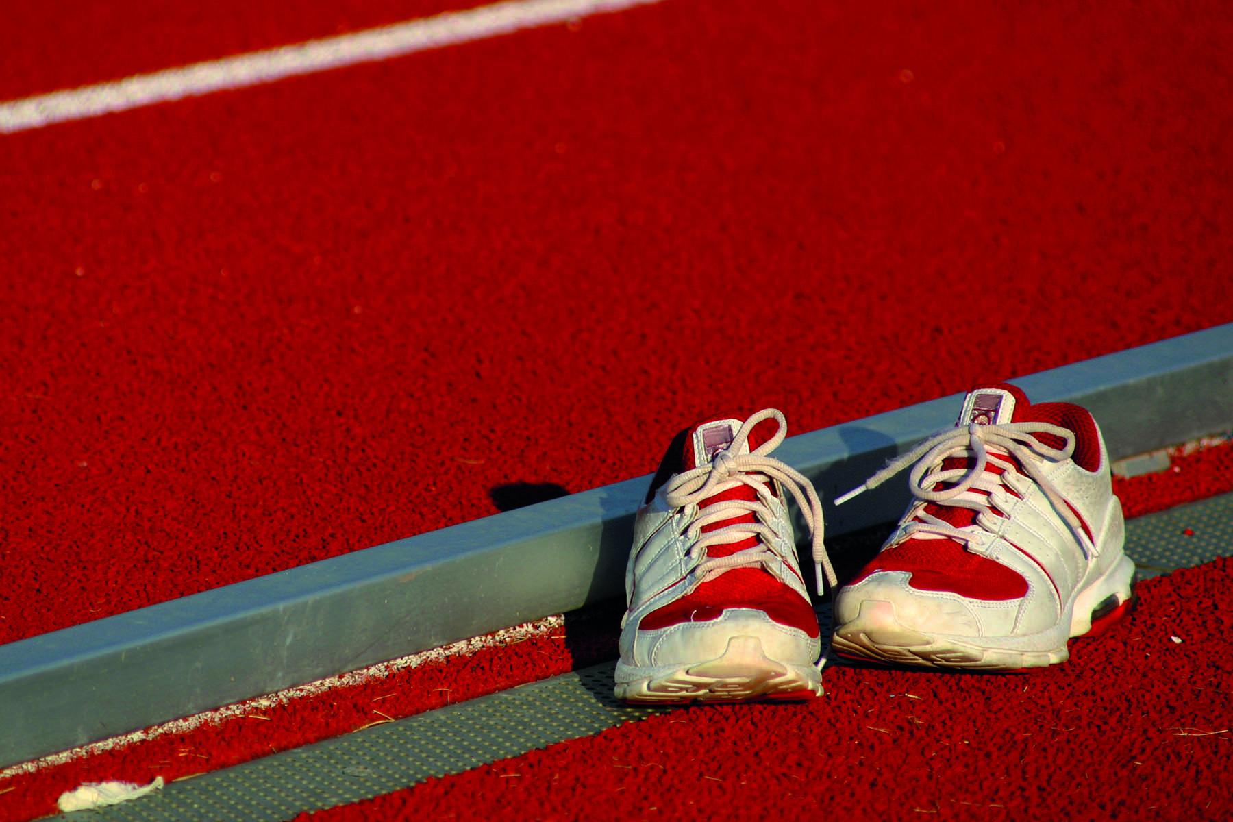 Ett par röda gymnastikskor på en röd träningsbana