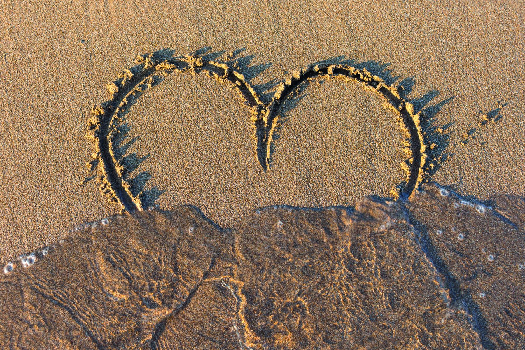 Ett hjärta skrivet i sanden sköljs bort av en våg