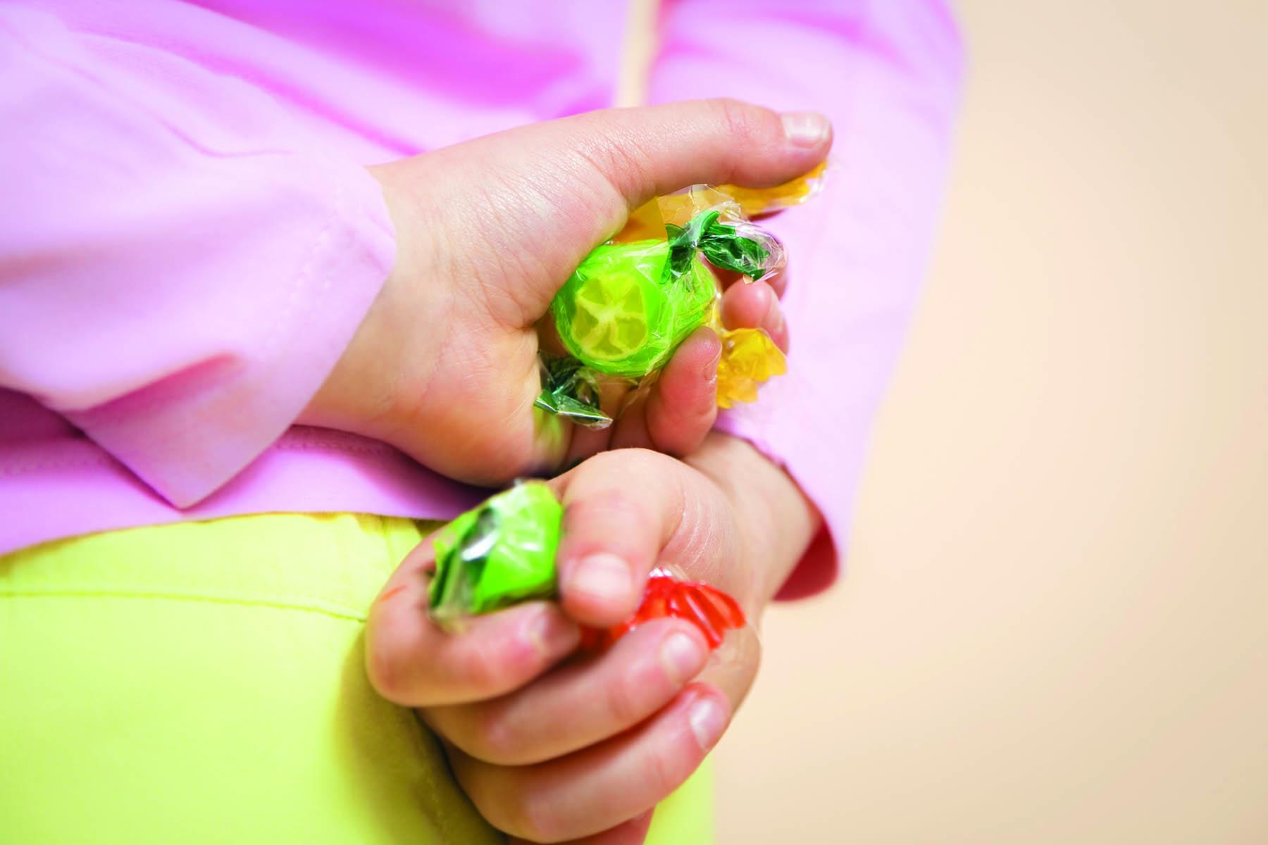 Ett barn döljer godis bakom ryggen