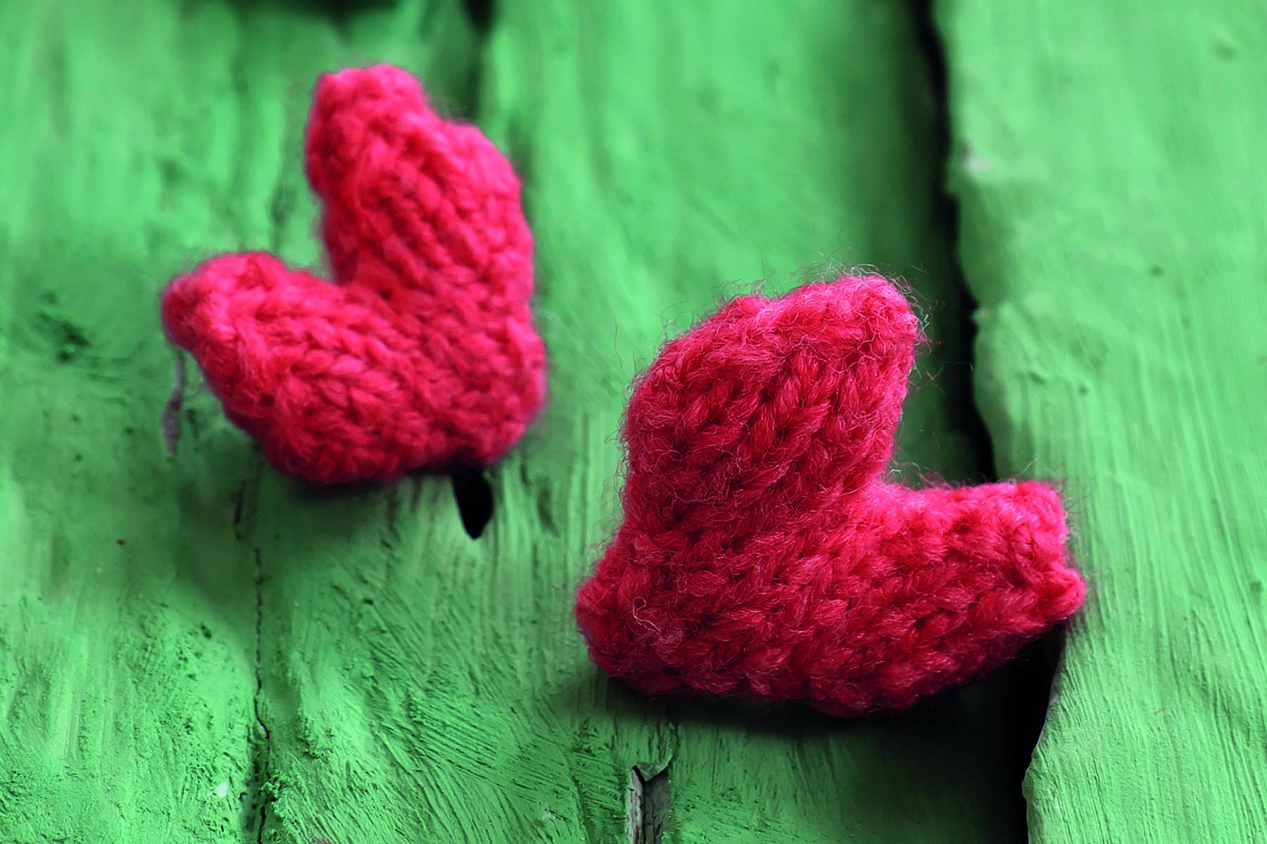 Två röda garnhjärtan på ett grönt träunderlag