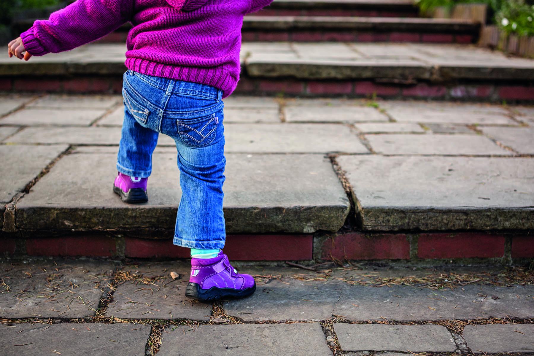 Ett barns ben bakifrån som tar sig upp för en trappa