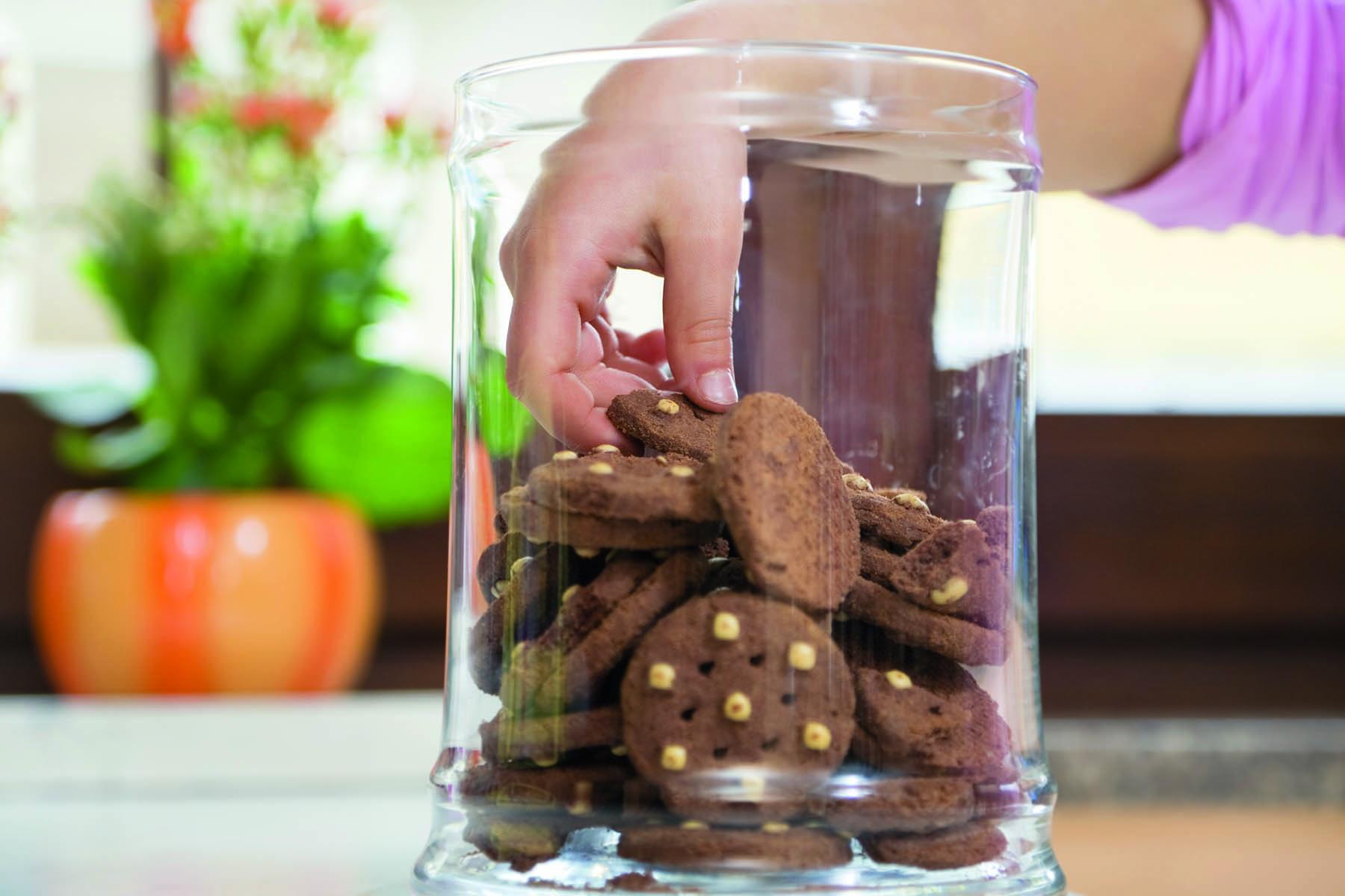 Ett barns hand i en glasburk med kakor