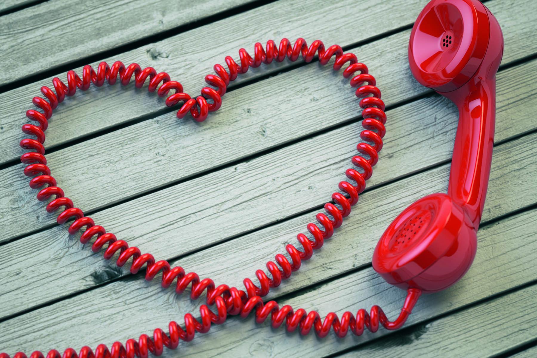 En röd telefonlur vars sladd formas till ett hjärta