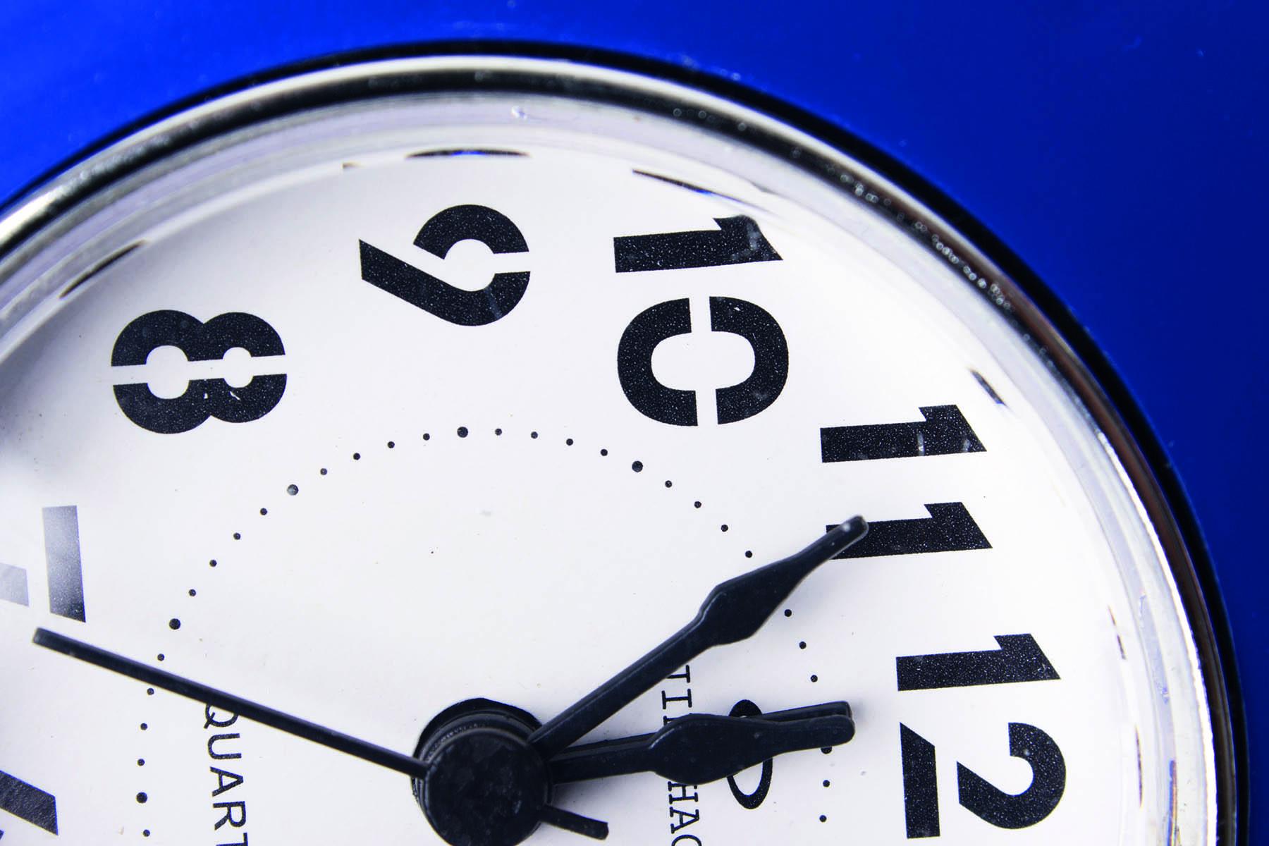 Liggande klocka som visar fem i tolv
