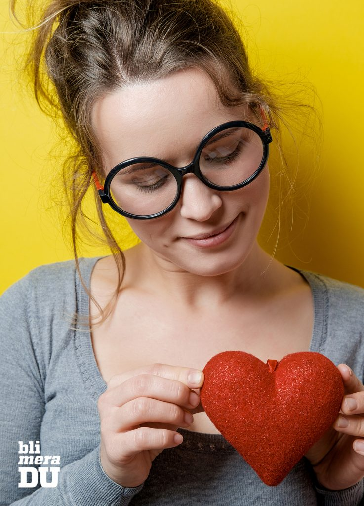 Kvinna i glasögon som betraktar ett rött tyghjärta framför sitt eget hjärta.