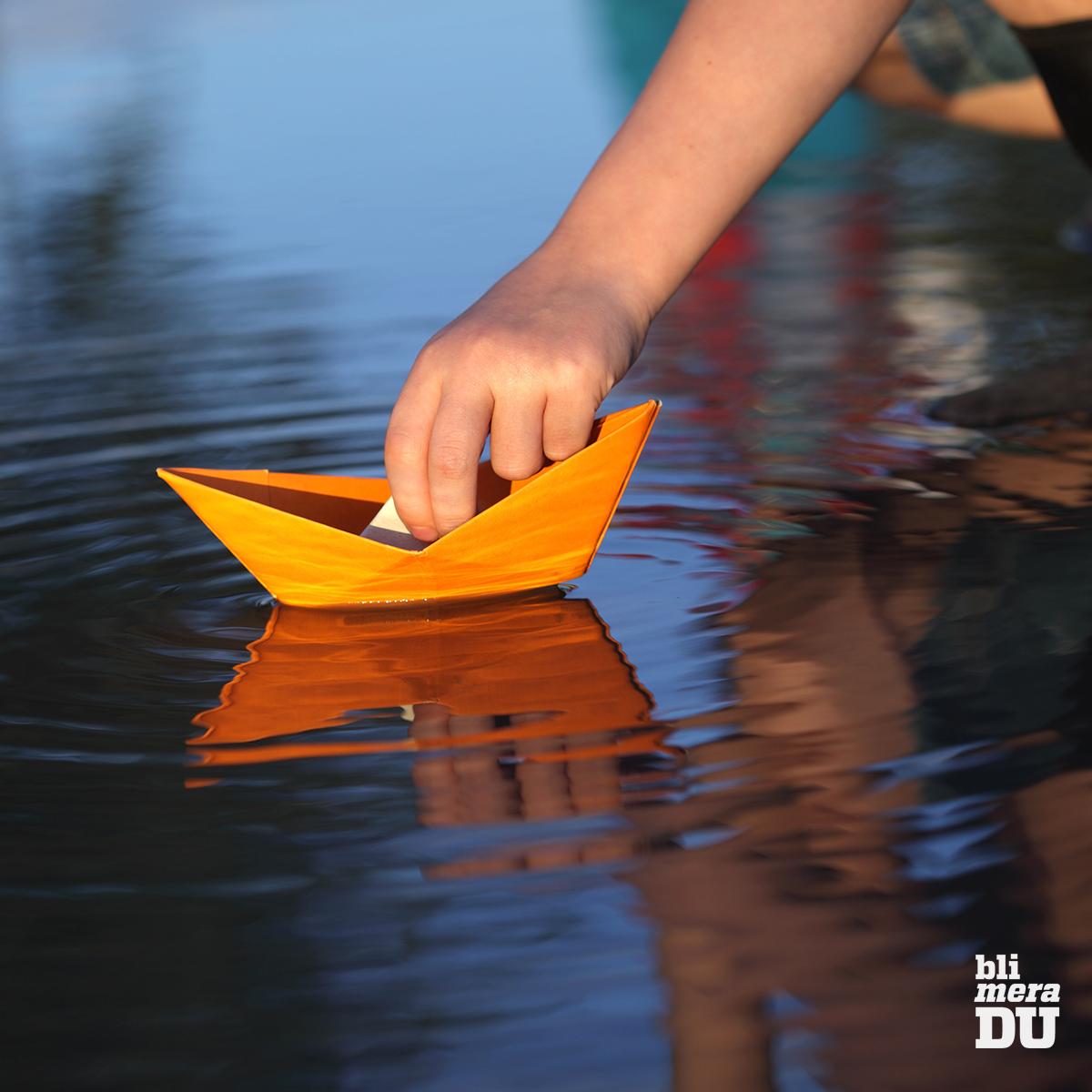 Pojke sjösätter orange pappersbåt