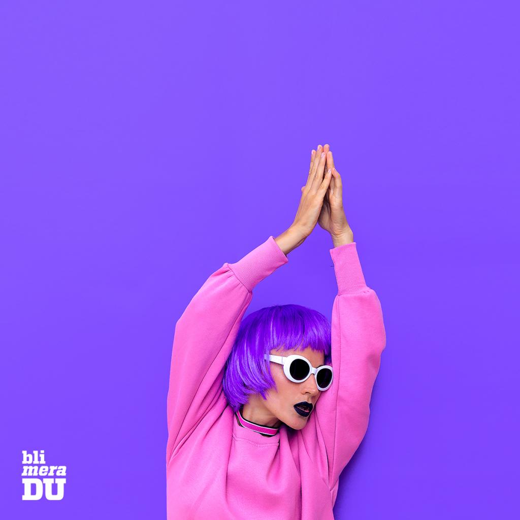 Ung kvinna som dansar i lila peruk