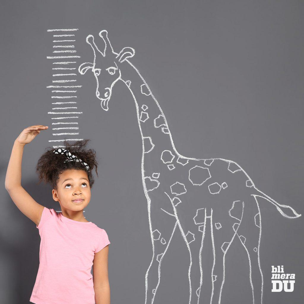 Liten flicka som mäter sig mot en skala som är uppmålad på en vägg