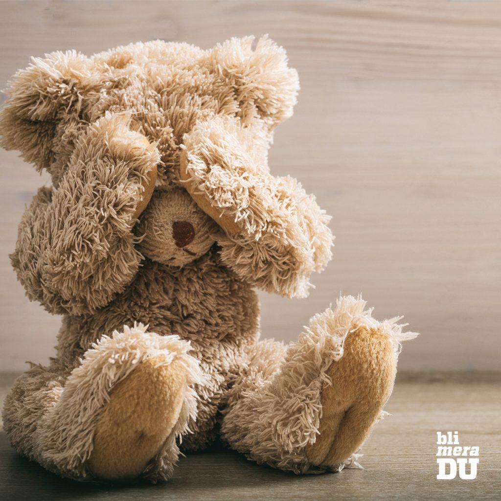 Nallebjörn som håller tassarna framför ögonen.